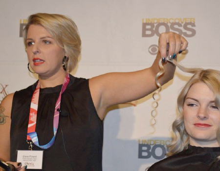 Close up of a woman curling a client's hair.
